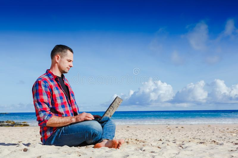 Young man with laptop working on the sand beach royalty free stock images