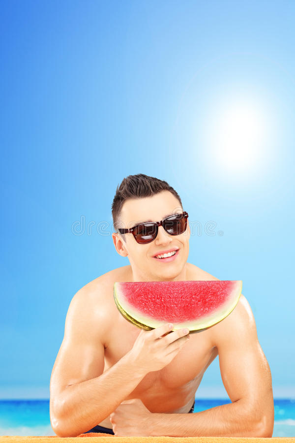 Download Young Man Laying On A Towel And Eating A Slice Of Watermelon Stock Image - Image: 32036025