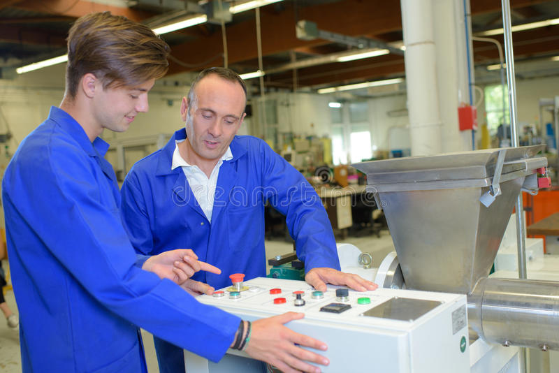 Young man learning controls machine. Young men learning controls of machine stock photo
