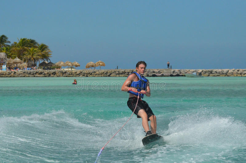 Young Man in a Life Vest Riding a Wakeboard. Young man riding a wakeboard with a life vest off of Aruba royalty free stock photos