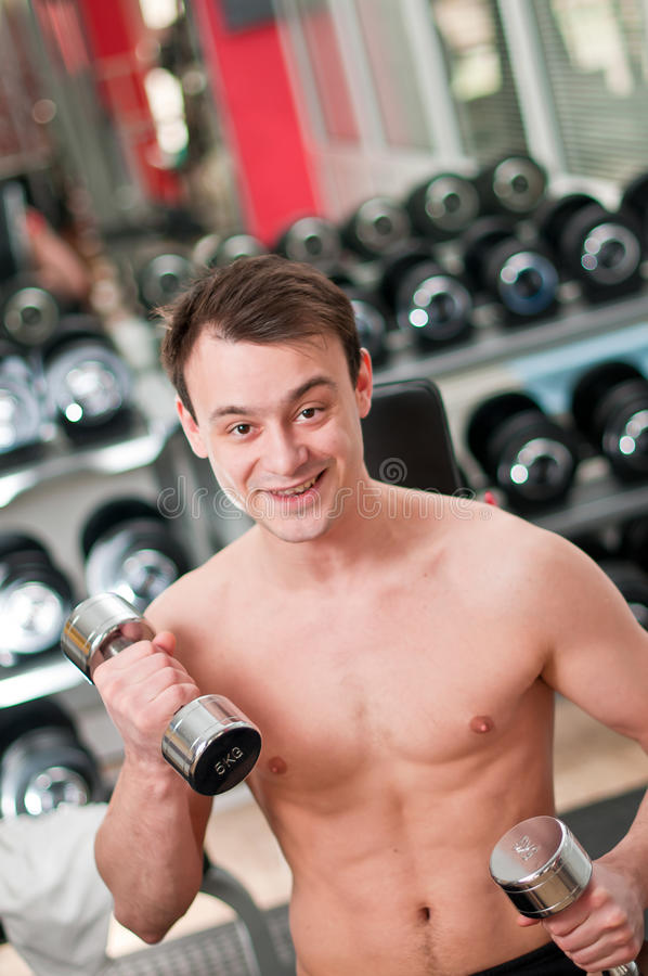 Download Young man lifting bumbbell stock image. Image of metal - 19022029