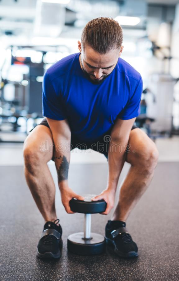 Young man lifting dumbbell at the gym. royalty free stock images