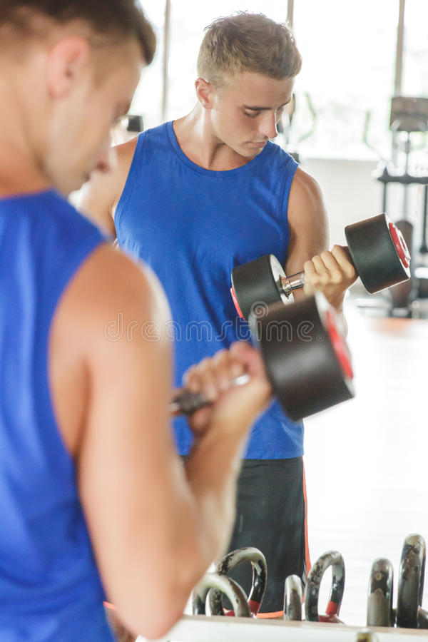 Young man lifting dumbbell with his reflection on mirror. Portrait of young man lifting dumbbell with his reflection on mirror at the gym royalty free stock image