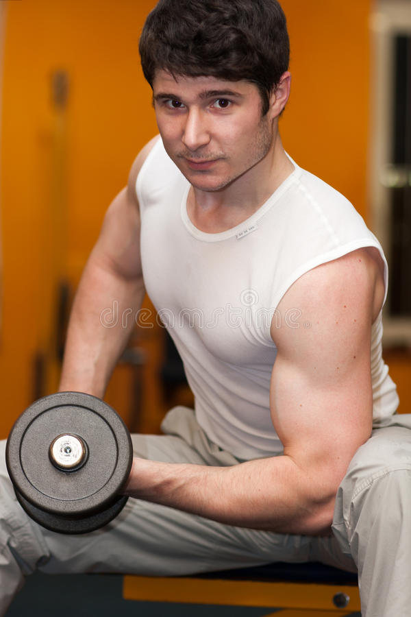 Young man lifting dumbell at fitness gym. Young sportsman lifting dumbell at fitness gym stock photography