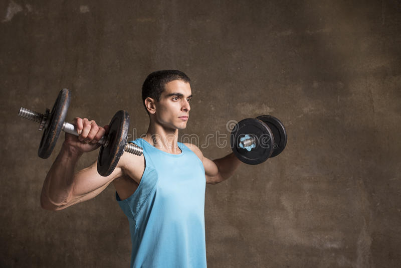 Young man lifting weights. In studio shot with wall background stock images