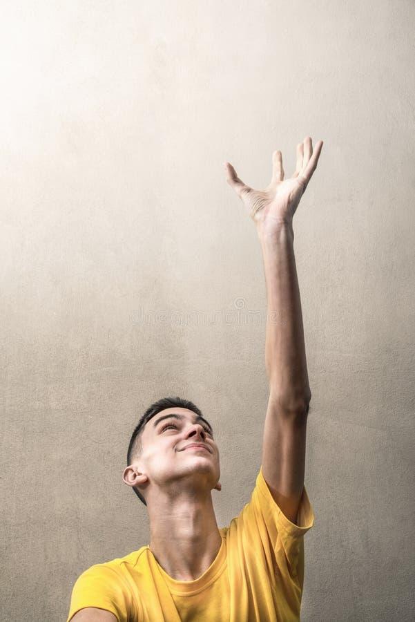 Young man lifts his arms upwards stock photos
