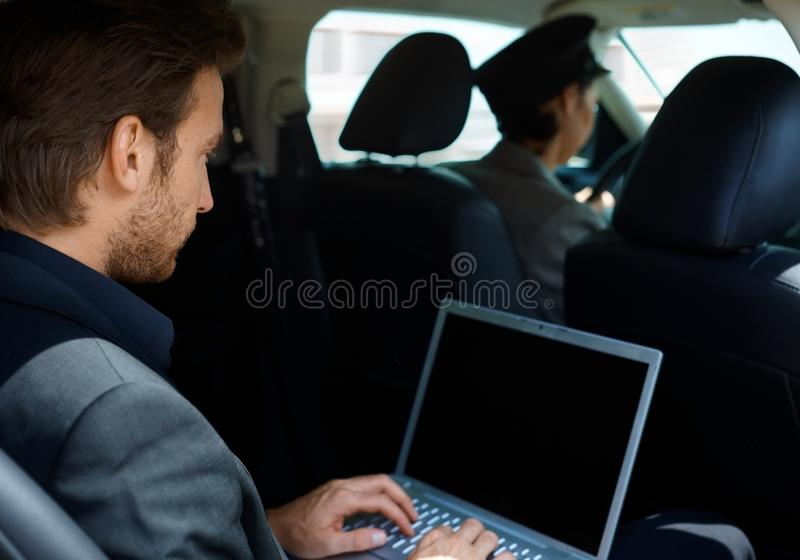 Young man in limousine using laptop computer. Young men in limousine working on laptop computer royalty free stock photo