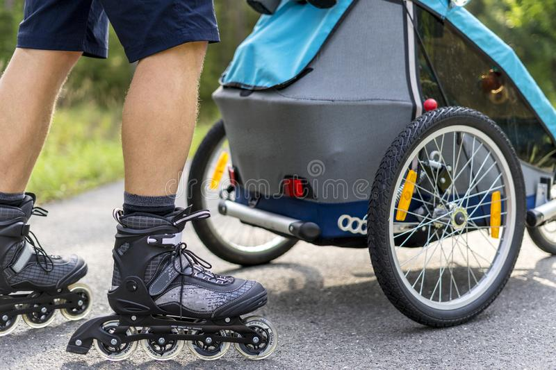 Young man in line skating outdoors with baby stroller stock photos