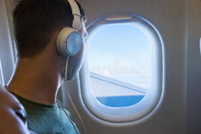 Young man listening music and looking out the window of an flying airplane stock photo