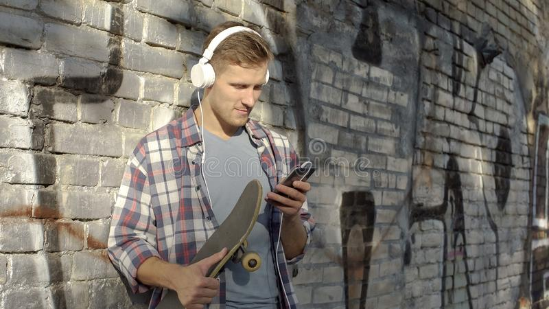 Young man listening to music and scrolling on cellphone, holding skateboard stock photo
