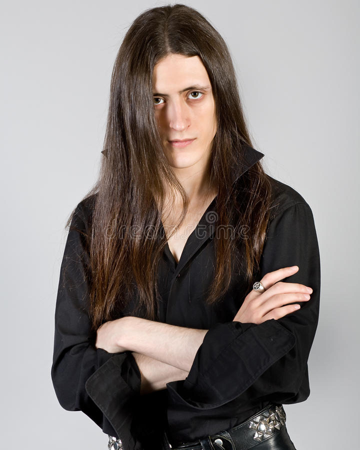Young man with long hair. Portrait of the young man with long hair in black clothes stock images