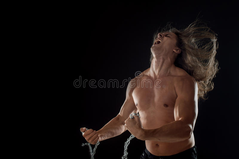 Young man with long hair breaks the iron chain. Strong. Concept of resistance. Young man with long hair breaks the iron chain royalty free stock photo