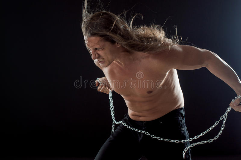 Young man with long hair breaks the iron chain. Strong. Concept of resistance. Young man with long hair breaks the iron chain royalty free stock photography