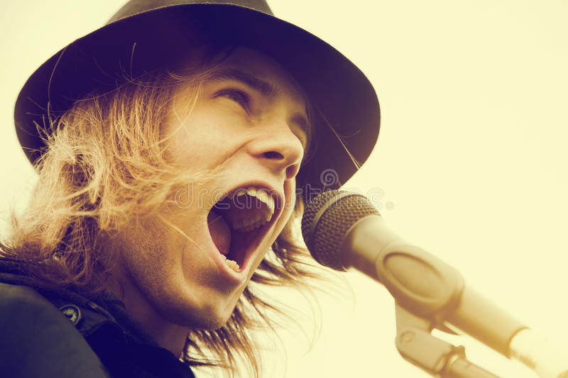 Young man with long hair and hat shouting to microphone. Vintage, music. Young man with long hair and hat singing, shouting to microphone. Vintage, music royalty free stock photography