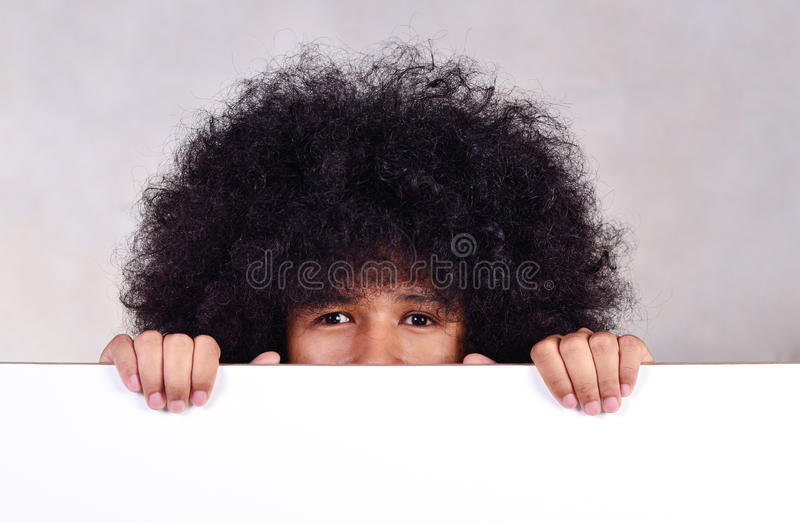 Young man with long hair holding whiteboard. Close up young man with long hair holding whiteboard stock image