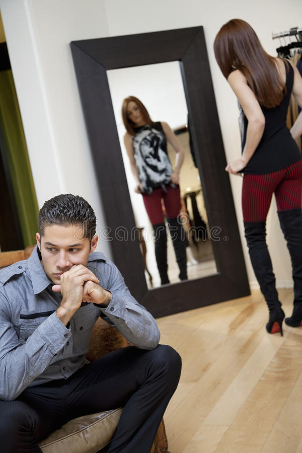 Young Man Looking Away While Thinking With Girlfriend In Background Looking At Herself In Mirror Royalty Free Stock Image