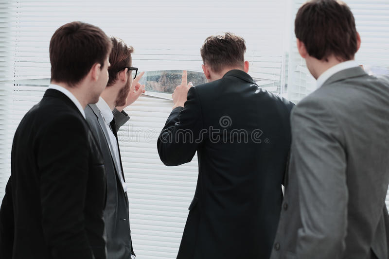 Young man looking through the blinds of the window in the office royalty free stock photography