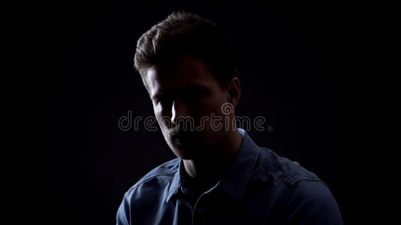 Young man looking at camera isolated on black background, personality dark side stock images