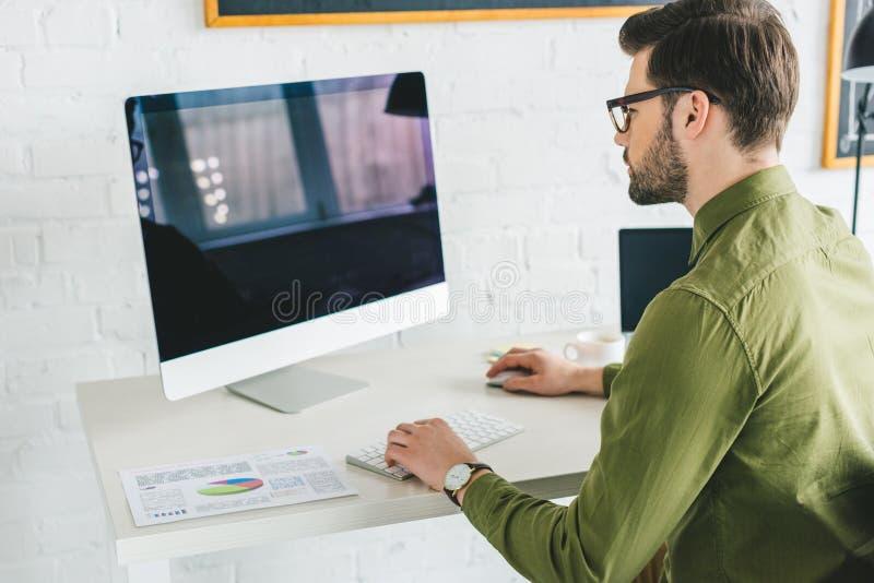 Young man looking at computer screen royalty free stock photography