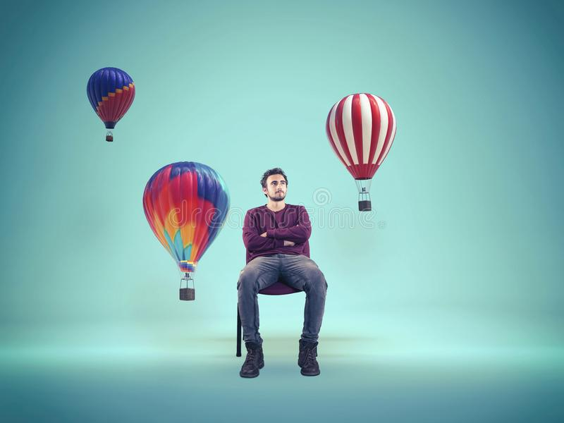 Young man looking. The concept of creative mind. Young man looking at color hot air balloons. The concept of creative mind royalty free stock photos