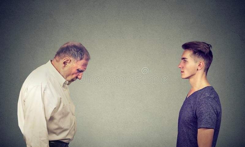 Young man looking at elder depressed himself royalty free stock photo