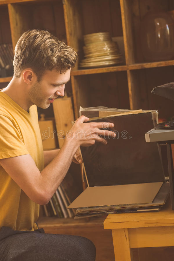 Young man looking at his vinyl collection. At home in the living room stock image