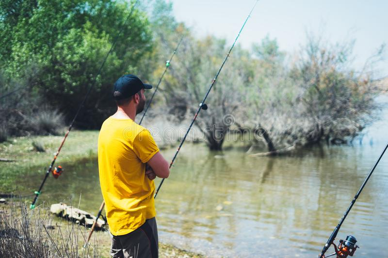 Young man looking on horizont seascape and holds a fishing rod and catches fish in the nature background, hipster fisherman spends. Vacation on the blue ocean stock photography