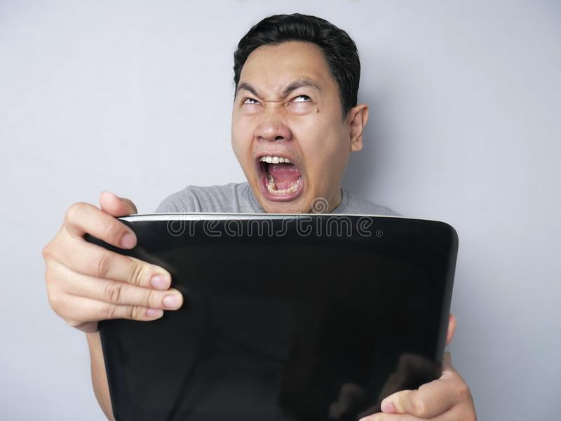 Young Man Looking at Laptop, Angry Gesture royalty free stock image
