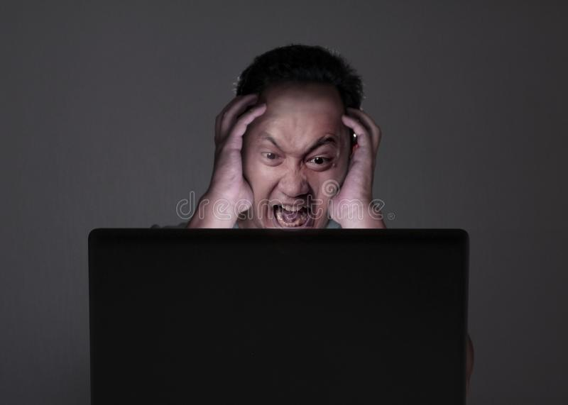 Young Man Looking at Laptop, Angry Gesture royalty free stock photo