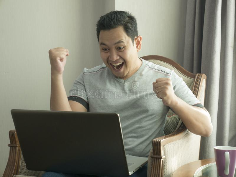 Young Man Looking at Laptop, Winning Gesture. Young Asian man wearing casual grey shirt looking at laptop while sitting on couch, winning gesture. Successful stock images