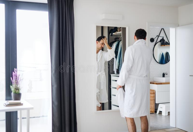 Young man looking in mirror in bedroom in the morning, daily routine. A young man looking in mirror in bedroom in the morning, daily routine royalty free stock photography