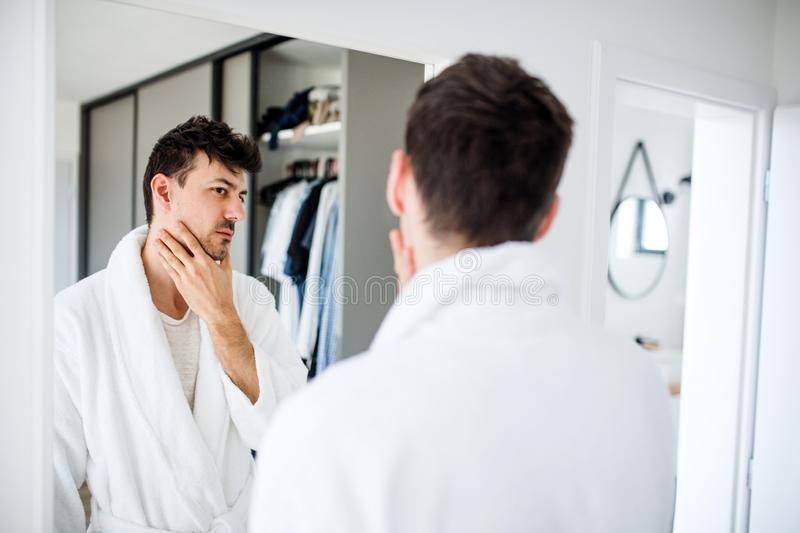Young man looking in mirror in bedroom in the morning, daily routine. A young man looking in mirror in bedroom in the morning, daily routine stock photography