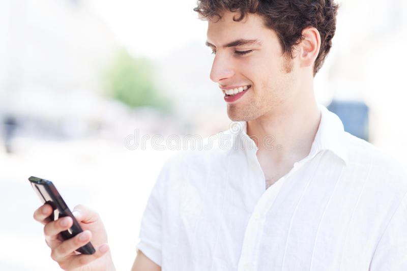 Young Man Looking At Mobile Phone Stock Photo