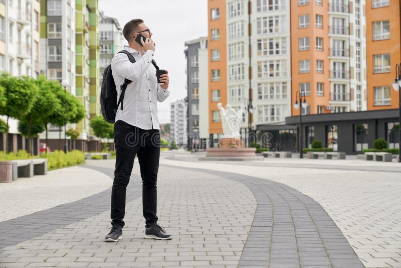 Young man looking at multistory houses, talking by phone. royalty free stock images