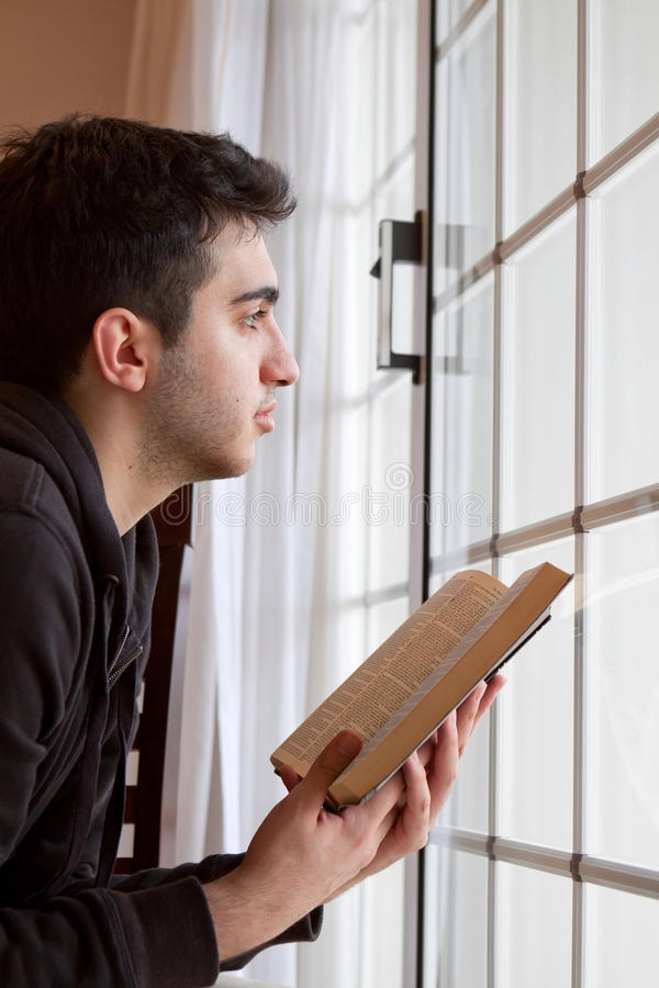 Man Holding Bible Looking Out Window. Young man looking outside with open Bible in hand stock images
