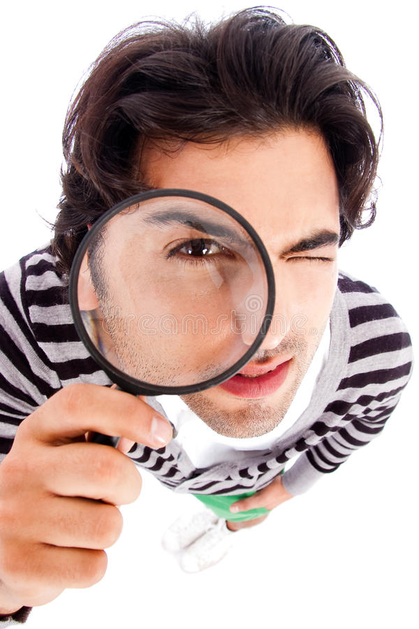 Young man looking up with a magnifying glass stock images