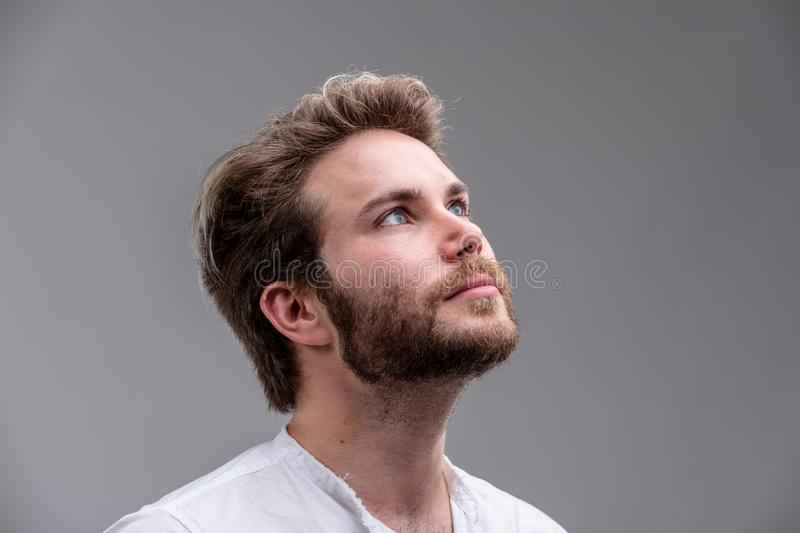 Young man looking up while thinking of a new idea stock images