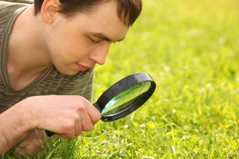 Young man looks through magnifier stock photo
