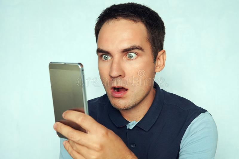 Young man looks at the phone and is surprised by what he saw. Puzzled frightened expression on the face of a guy reading stock photos