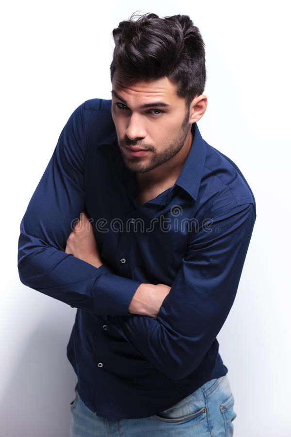Young man looks at you with arms folded royalty free stock images