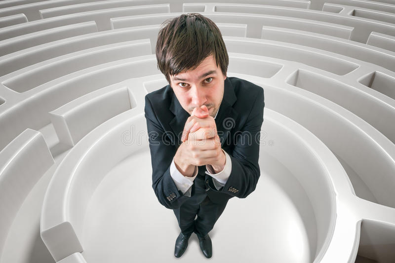 Young man is lost in maze and is asking for help to find exit. 3D rendered illustration of maze.  royalty free stock photos