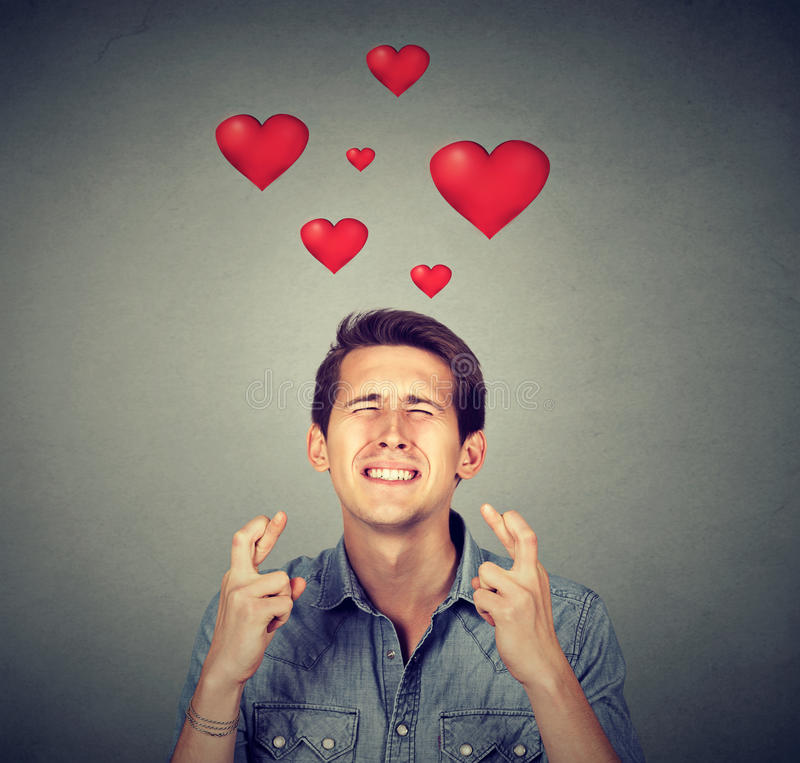Young man in love making a wish. On gray background royalty free stock photo