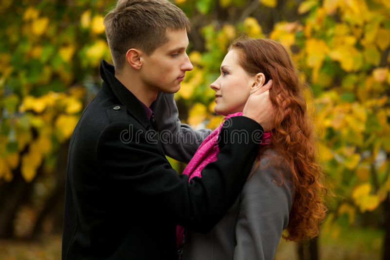 Young man lovingly looks at his girlfriend royalty free stock photo