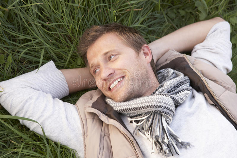 Young man lying alone on grass stock photos