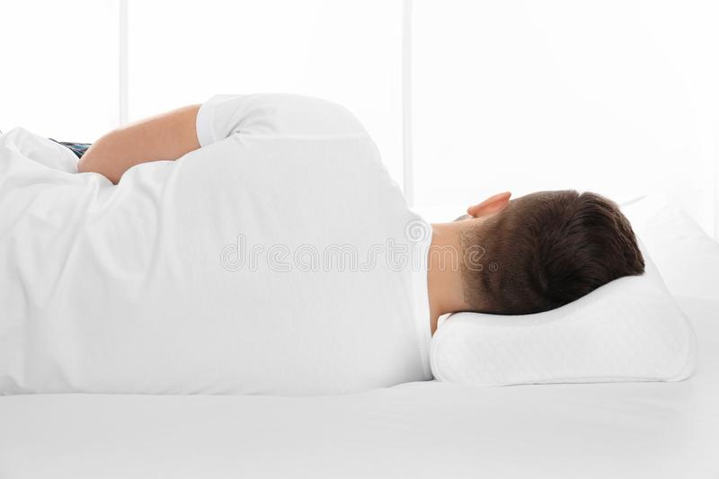 Young man lying on bed with orthopedic pillow. Against white background. Healthy posture concept royalty free stock photos