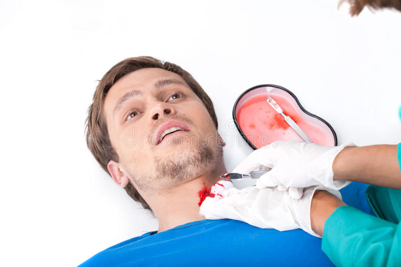 Young man lying on floor with blood on neck. stock photos