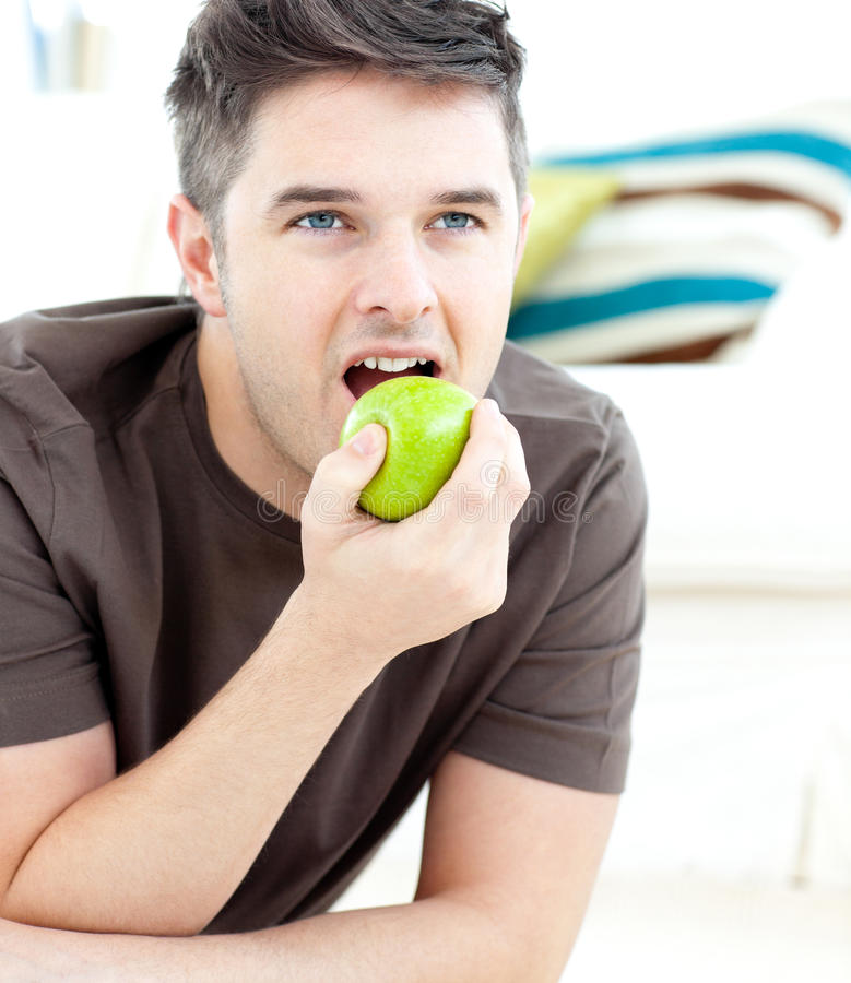 Download Young Man Lying On The Floor And Eating An Apple Stock Image - Image: 15427823