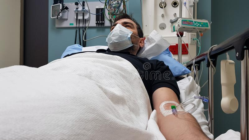 Young man lying in hospital bed. Recovering in modern hospital wards, covered with blanket, face mask and with intravenous needle stock image