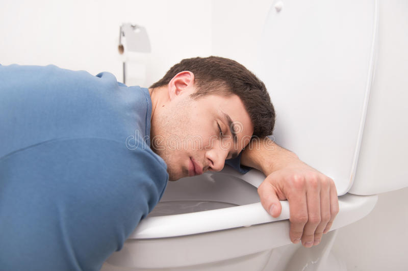 Young man lying on toilet seat. Guy kneeling over toilet seat and sleeping stock images