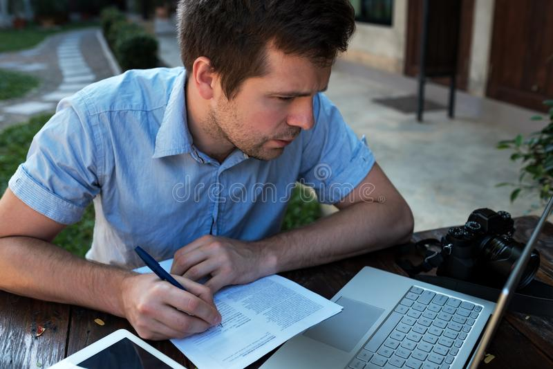 A young man makes a business plan for his personal business. royalty free stock image